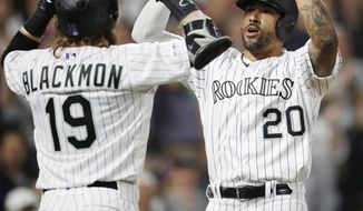 Colorado Rockies' Charlie Blackmon, left, congratulates Ian Desmond on his grand slam off San Diego Padres relief pitcher Robbie Erlin during the fifth inning of a baseball game Saturday, June 15, 2019, in Denver. (AP Photo/David Zalubowski)