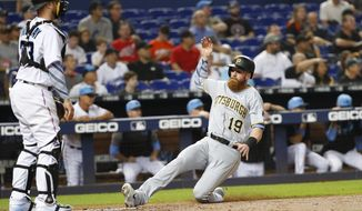 Pittsburgh Pirates' Colin Moran (19) slides into home as Miami Marlins catcher Bryan Holaday looks on during the fourth inning of a baseball game, Sunday, June 16, 2019, in Miami. Moran scored on a double by Jung Ho Kang. (AP Photo/Wilfredo Lee)
