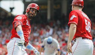 Cincinnati Reds' Jesse Winker, left, celebrates as he runs the bases after hitting a two-run home run off Texas Rangers starting pitcher Ariel Jurado in the fourth inning of a baseball game, Sunday, June 16, 2019, in Cincinnati. (AP Photo/John Minchillo)