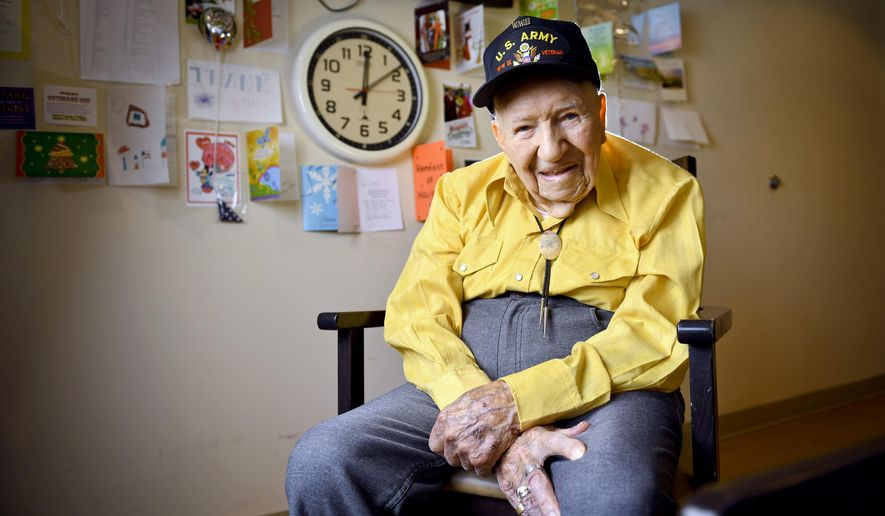 FILE - In this May 6, 2019, file photo, John R. Frey, a U.S. Army veteran, poses for a portrait next to cards and mementos he has been given at the Mervyn Sharp Bennion Central Utah Veterans Home in Payson, Utah. Frey, a World War II veteran whose family hoped to help him get 101 cards for his 101st birthday say they have been overwhelmed and grateful as well over 5,000 cards have been sent to Frey.  (Isaac Hale/The Daily Herald via AP, File)
