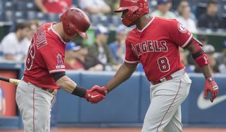 Los Angeles Angels' Justin Upton (8) is greeted by teammate Kole Calhoun after hitting a home run against the Toronto Blue Jays during second-inning baseball game action in Toronto, Monday, June 17, 2019. (Fred Thornhill/The Canadian Press via AP)