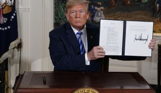 FILE - In this May 8, 2018 file photo President Donald Trump shows a signed Presidential Memorandum after delivering a statement on the Iran nuclear deal from the Diplomatic Reception Room of the White House. Iran said Monday, June 17, 2019, it will break the uranium stockpile limit set by Tehran's nuclear deal with world powers in the next 10 days. (AP Photo/Evan Vucci, File)