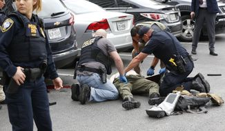 Law enforcement officers attend to an injured shooter in a parking lot after he fired shots at the Earle Cabell Federal Building in downtown Dallas, Monday, June 17, 2019. (Tom Fox/The Dallas Morning News)