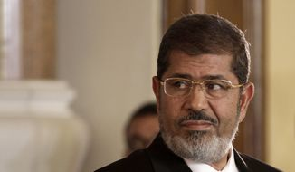 In this July 13, 2012, photo, Egyptian President Mohammed Morsi holds a news conference with Tunisian President Moncef Marzouki, at the Presidential palace in Cairo, Egypt. On Monday, June 17, 2019, Egypt's state TV said that the country's ousted President Mohammed Morsi has collapsed during a court session and died. (AP Photo/Maya Alleruzzo, File)