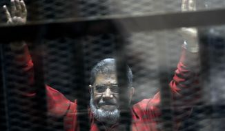 FILE - In this June 21, 2015 file photo, former Egyptian President Mohammed Morsi, wearing a red jumpsuit that designates he has been sentenced to death, raises his hands inside a defendants cage in a makeshift courtroom at the national police academy, in an eastern suburb of Cairo, Egypt. On Monday, June 17, 2019, Egypt's state TV said that the country's ousted President Mohammed Morsi has collapsed during a court session and died. (AP Photo/Ahmed Omar, File)
