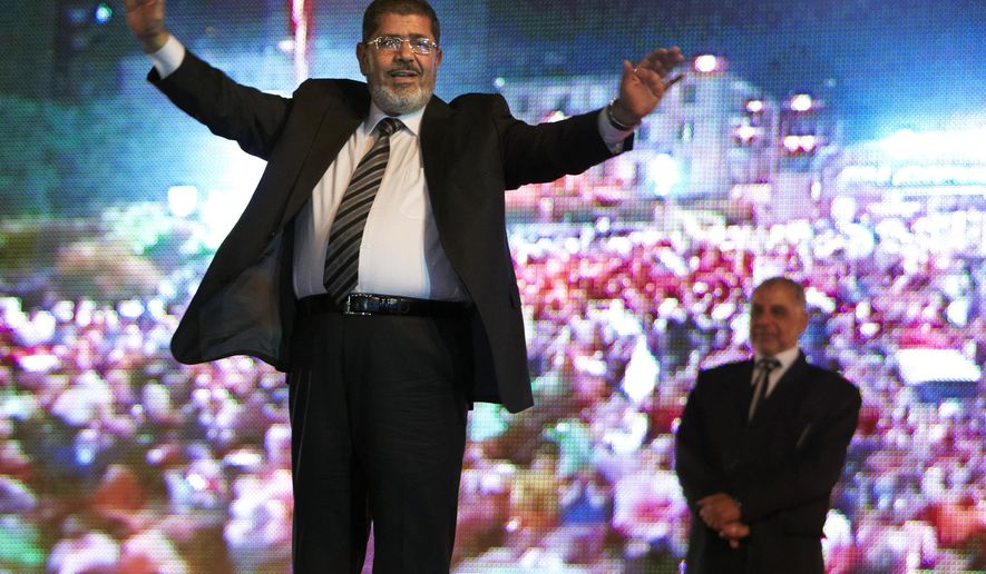 FILE - In this May 20, 2012 file photo, then Muslim Brotherhood's presidential candidate Mohammed Morsi holds a rally in Cairo, Egypt. On Monday June 17, 2019, Egypt's state TV says the country's ousted President Mohammed Morsi, 67, collapsed during a court session and died. It said it occurred while he was attending a court trial on Monday on espionage charges. Morsi, who hailed from Egypt's largest Islamist group, the now outlawed Muslim Brotherhood, was elected president in 2012 in the country's first free elections following the ouster the year before of longtime leader Hosni Mubarak. (AP Photo/Fredrik Persson, File)