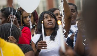 Sherika Logan looks up during a vigil for Eric Logan Monday, June 17, 2019 on Washington Street in South Bend, Ind.  Logan, 54, was killed in South Bend early Sunday after someone called police to report a suspicious person going through cars, according to the St. Joseph County prosecutor's office. (Michael Caterina/South Bend Tribune via AP)