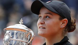 Australia's Ashleigh Barty holds the trophy as she celebrates winning her women's final match of the French Open tennis tournament against Marketa Vondrousova of the Czech Republic in two sets 6-1, 6-3, at the Roland Garros stadium in Paris, Saturday, June 8, 2019. (AP Photo/Christophe Ena)