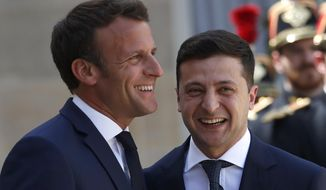 French President Emmanuel Macron, left, greets Ukrainian President Volodymyr Zelenskiy before a meeting at the Elysee Palace, in Paris, Monday, June 17, 2019. (AP Photo/Christophe Ena)