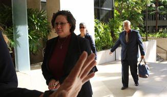 FILE - In this May 22, 2019, file photo, former Honolulu deputy city prosecutor Katherine Kealoha, left, and her husband, ex-police chief Louis Kealoha, right, walk into federal court in Honolulu. In the midst of Hawaii's largest corruption trial, a judge is allowing an additional attorney to represent a former Honolulu prosecutor accused of using her police chief husband's job to frame her uncle. Monday, June 17, 2019, marks the 13th day of trial against Katherine and Louis Kealoha and current and former officers. The judge appointed taxpayer-funded lawyers for the Kealohas after reviewing financial records that show they can't afford lawyers. (AP Photo/Caleb Jones, File)