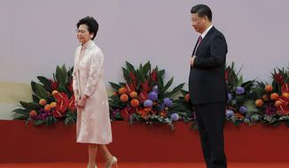 In this Saturday, July 1, 2017, file photo, Chinese President Xi Jinping, right, looks at Hong Kong's new Chief Executive Carrie Lam after administering the oath for a five-year term in office at the Hong Kong Convention and Exhibition Center in Hong Kong. (AP Photo/Kin Cheung) **FILE**