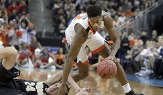 In this March 30, 2019, file photo, Virginia's De'Andre Hunter dribbles past Purdue's Grady Eifert (24) during the first half of a men's NCAA Tournament college basketball South Regional final game, in Louisville, Ky. Hunter is a high prospect in the NBA Draft on Thursday, June 20. (AP Photo/Michael Conroy, File) **FILE**
