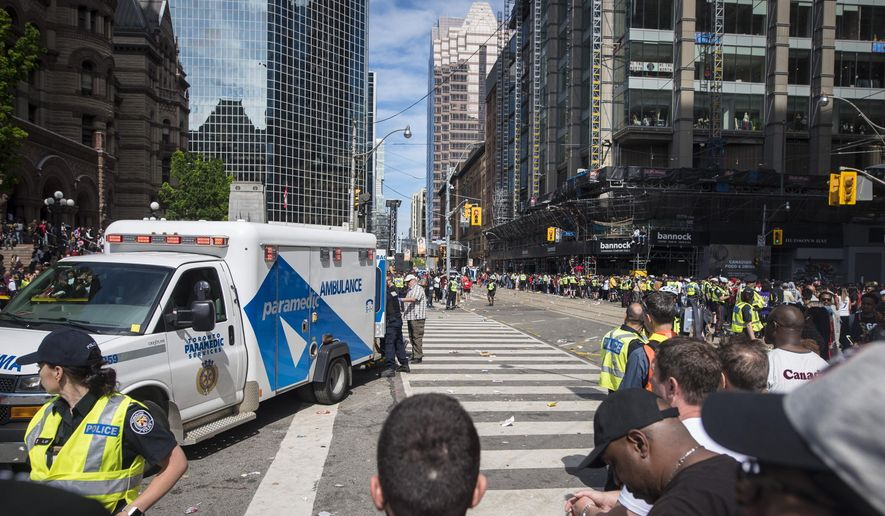 An ambulance arrives to the scene after shots were fired during the Toronto Raptors NBA basketball championship victory celebration near Nathan Phillips Square in Toronto, Monday, June 17, 2019. (Tijana Martin/The Canadian Press via AP)