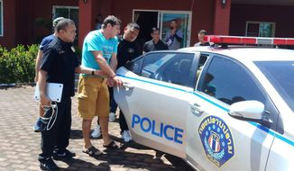 In this June 15, 2019, photo released by Crime Suppression Division, Italian Francesco Galdeli, center, is detained by Thai police officers at a house in Chonburi. Thai police said they have arrested the Italian man wanted in his home country after fleeing a jail sentence handed down for fraudulently using the name of actor George Clooney to lure people into investing in a bogus clothing company. (Crime Suppression Division of Thailand via AP)