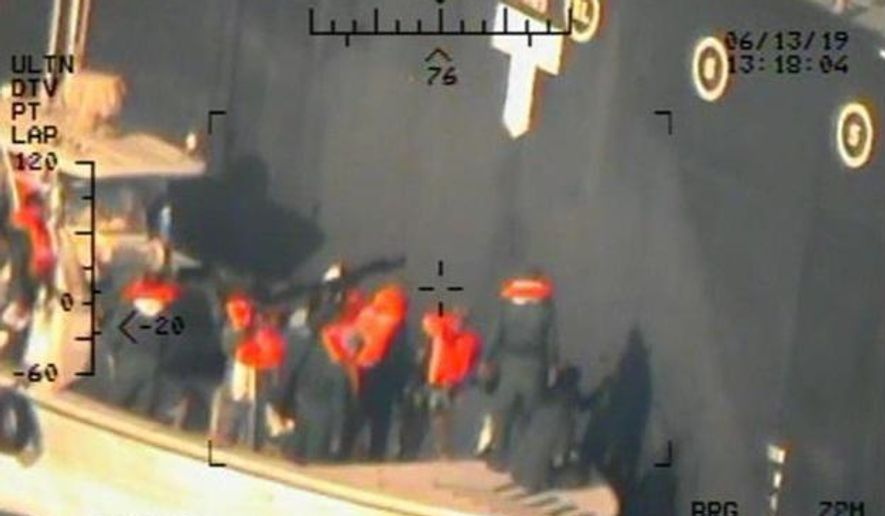 This image released by the U.S. Department of Defense on Monday, June 17, 2019, and taken from a U.S. Navy helicopter, shows what the Navy says are members of the Islamic Revolutionary Guard Corps Navy removing an unexploded limpet mine from the M/T Kokuka Courageous. (U.S. Department of Defense via AP)