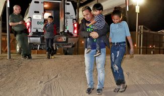 "FILE - In this July 18, 2018 file photo, a Honduran man carries his 3-year-old son as his daughter and other son follow to a transport vehicle after being detained by U.S. Customs and Border Patrol agents in San Luis, Ariz. Federal judges in California have challenged more of the Trump administration's ""zero-tolerance"" policy on illegal immigration. Their decision in Sept. 2018 to no longer accept pleas at initial appearances led to the dismissal of many cases because the government deported defendants before they could return to court. The judges' stance is another example of how the judiciary, in ways large and small, has put the brakes on some of the administration's efforts to curb immigration. (AP Photo/Matt York, File)"
