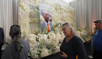 Fans file past a wall of flowers with a portrait of Denver Broncos owner Pat Bowlen placed in the center during a memorial Tuesday, June 18, 2019, at Mile High Stadium, the NFL football team's home in Denver. Bowlen, who has owned the franchise for more than three decades, died last Thursday. (AP Photo/David Zalubowski)