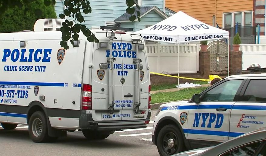 In this image taken from video provided by WABC-TV, New York City Police department vehicles are parked near a crime scene outside Crocheron Park in the Queens borough of New York, Tuesday, June 18, 2019. Police say what appeared to be a dead infant in a grassy area outside the park turned out to be a realistic-looking doll. (WABC-TV via AP)