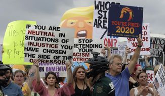 Protestors hold up anti President Donald Trump signs during a rally Tuesday, June 18, 2019, in Orlando, Fla. A large group of protestors were holding a rally near where Trump was announcing his re-election campaign. (AP Photo/Chris O'Meara)