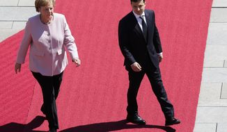 German Chancellor Angela Merkel, left, and Ukrainian President Volodymyr Zelenskiy, right, review the honour guards during the welcoming ceremony prior to a meeting at the chancellery in Berlin, Germany, Tuesday, June 18, 2019. (AP Photo/Markus Schreiber)