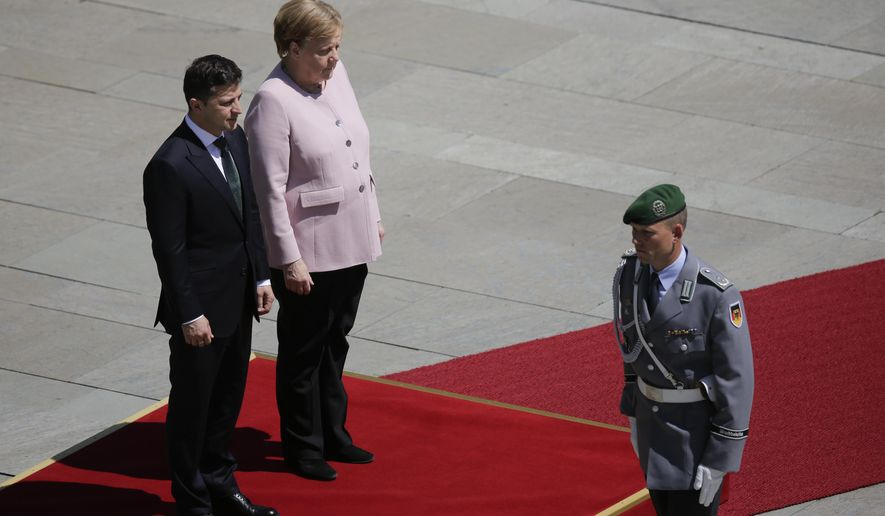 German Chancellor Angela Merkel, on the podium right, and Ukrainian President Volodymyr Zelenskiy, on the podium left, listen to the national anthems during the welcoming ceremony, prior to a meeting at the chancellery in Berlin, Germany, Tuesday, June 18, 2019. (AP Photo/Markus Schreiber)