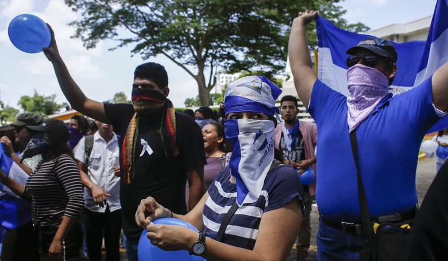 Students, many hiding their identify for fear of being identified and later targeted by security forces or government supporters, protest inside the Central American University (UCA) where security forces cannot legally enter, as they demand the release of all political prisoners in Managua, Nicaragua, Tuesday, June 18, 2019, the last day of a 90-day period for releasing such prisoners, which was agreed to during negotiations between the government and opposition. (AP Photo/Alfredo Zuniga) ** FILE **