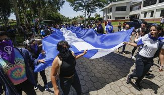 Students, some hiding their identify for fear of being identified and later attacked by security forces or government supporters, protest inside the Central American University (UCA) where security forces cannot legally enter to demand the release of all political prisoners in Managua, Nicaragua, Tuesday, June 18, 2019, the last day of a 90-day period for releasing such prisoners as part of negotiations between the government and opposition. Nicaragua's government said Tuesday that it has released all prisoners detained in relation to 2018 anti-government protests, though the opposition maintains that more than 80 people it considers political prisoners are still in custody. (AP Photo/Alfredo Zuniga)