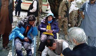 In this photo provided by Gilgit Baltistan regional police department, mountaineers receive initial treatment following their rescue, at a helipad in the town of Imit, Ghizer district of Gilgit Balistan region, Pakistan, Tuesday, Jun 18, 2019. A Pakistani army helicopter rescued on Tuesday four Italian and two Pakistani climbers stranded at an altitude of around 5,300 meters (17,390 feet) in the country's north, after an avalanche struck the team the previous day, a mountaineering worker said. A Pakistani member of the team was killed. (Gilgit Baltistan regional police department via AP)