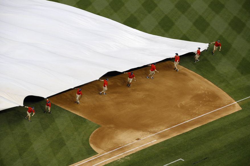 Grounds crew members pull a tarp over the infield during a rain delay before a baseball game between the Philadelphia Phillies and the Washington Nationals, Tuesday, June 18, 2019, in Washington. (AP Photo/Patrick Semansky) ** FILE **