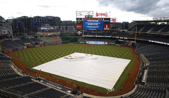 A tarp covers the infield during a rain delay before a baseball game between the Philadelphia Phillies and the Washington Nationals, Tuesday, June 18, 2019, in Washington. (AP Photo/Patrick Semansky)