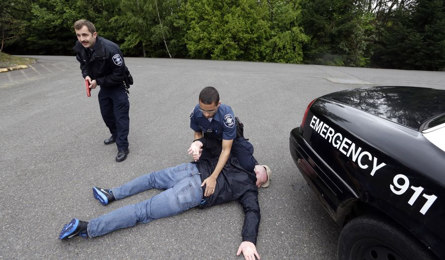 In this photo taken May 6, 2015, Seattle police recruits Travis Duennes, left, and Tre Smith work together through a practice scenario at the Washington State Criminal Justice Training Commission in Burien, Wash.  While some critics say that good officers already consider themselves protectors and that police need the best equipment to defend themselves and the public, many law enforcement leaders see a need for a broader change in police training and culture.  (AP Photo/Elaine Thompson)