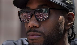 Cheering fans are reflected in the sunglasses of Toronto Raptors' Kawhi Leonard during the team's NBA basketball championship parade in Toronto, Monday, June 17, 2019. (Frank Gunn/The Canadian Press via AP) **FILE**