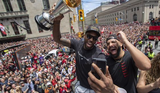 Toronto Raptors' Kawhi Leonard holds his MVP trophy while celebrating with rapper/producer Drake during the team's NBA basketball championship parade in Toronto, Monday, June 17, 2019. (Frank Gunn/The Canadian Press via AP)