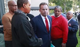 FILE- In this Jan. 11, 2019, file photo, suspended Broward County Sheriff Scott Israel, center, leaves a news conference surrounded by supporters in Fort Lauderdale, Fla., after Florida Gov. Ron DeSantis suspended him. Israel's lawyer says DeSantis' decision to suspend the sheriff who oversaw the response to the Parkland school shooting was a knee-jerk reaction based on politics. Those comments came Tuesday, June 18, 2019, at the beginning of a state Senate hearing as Scott Israel fights his suspension as Broward County sheriff. (AP Photo/Wilfredo Lee, File)