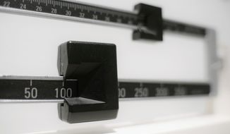This April 3, 2018, file photo shows a closeup of a beam scale in New York. A study released on Tuesday, June 18, 2019, found U.S. preschoolers on government food aid have grown a little less pudgy, offering fresh evidence that previous signs of shrinking obesity weren't a fluke. Obesity rates dropped to about 14 percent in 2016, the latest data available and a steady decline from 16 percent in 2010, researchers from the federal Centers for Disease Control and Prevention reported.  (AP Photo/Patrick Sison, File) ** FILE **
