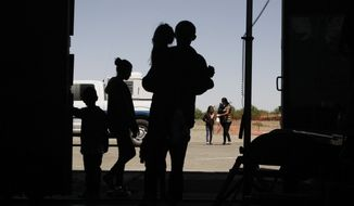 In this Wednesday, May 22, 2019, photo migrants mainly from Central America guide their children through the entrance of a World War II-era bomber hanger in Deming, N.M. A panel of appeals court judges in California will hear arguments in the long-running battle between advocates for immigrant children and the U.S. government over conditions in detention and holding facilities near the southwest border. (AP Photo/Cedar Attanasio) **FILE**