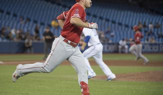 Los Angeles Angels' Mike Trout runs to first on single the drove in Justin Bour, off Toronto Blue Jays relief pitcher David Phelps during the ninth inning of a baseball game Wednesday, June 19, 2019, in Toronto. (Nathan Denette/The Canadian Press via AP)