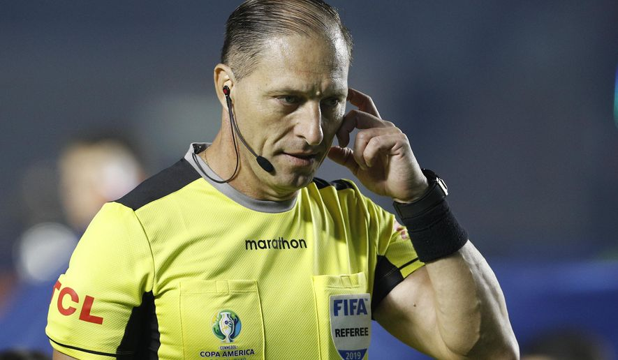Referee Nestor Pitana, of Argentina, speaks on his radio during a Copa America Group A soccer match between Brazil and Bolivia at the Morumbi stadium in Sao Paulo, Brazil, Friday, June 14, 2019. (AP Photo/Victor Caivano)