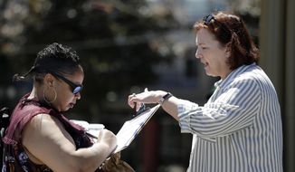 In this photo taken Monday, June 10, 2019, Seattle City Council candidate Pat Murakami, right, looks on as voter Lashaun Hartfield signs a replacement voucher for Murakami's campaign in Seattle. A first-of-its-kind public campaign finance program in Seattle gives voters vouchers worth $100 to pass on to any candidate they want. Now in its second election cycle, advocates say the program can level the political playing field, although its first round in Seattle showed mixed results. (AP Photo/Elaine Thompson)