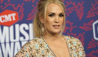 """FILE- In this June 6, 2019 file photo, Carrie Underwood arrives at the CMT Music Awards at the Bridgestone Arena in Nashville, Tenn. On Wednesday, June 19, 2019, a songwriting team filed a lawsuit against the singer, the NFL and NBC, saying they stole a song and used it to introduce """"Sunday Night Football"""" during the 2018-2019 season. (AP Photo/Sanford Myers, File)"""