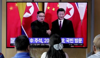 In this June 18, 2019 photo, people watch a TV news program reporting about Chinese President Xi Jinping's state visit to North Korea with a file footage of Chinese President Xi Jinping and North Korean leader Kim Jong Un, at the Seoul Railway Station in Seoul, South Korea. From nukes to huge food aid shipments to a shared skepticism about the United States, Xi and Kim will have a long list of topics to discuss when Xi heads north Thursday, June 20.(AP Photo/Lee Jin-man)