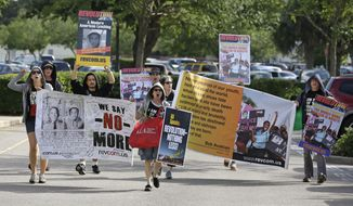 Members of the Revolutionary Communist Party, USA demonstrate outside the Seminole County Courthouse during the first day of trial for George Zimmerman, Monday, June 10, 2013, in Sanford, Fla. Zimmerman has been charged with second-degree murder for the 2012 shooting death of Trayvon Martin. (AP Photo/John Raoux)