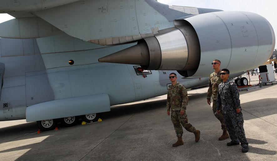 U.S. Air Force pilots based in England look on a Japan Kawasaki C-2 tactical military transport aircraft at Paris Air Show, in Le Bourget, north east of Paris, France, Tuesday, June 18, 2019. The world's aviation elite are gathering at the Paris Air Show with safety concerns on many minds after two crashes of the popular Boeing 737 Max. (AP Photo/ Francois Mori)