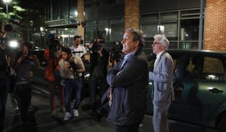 Michel Platini and his lawyer William Bourdon, right, answer reporters after Platini has been freed, outside the French police anti-corruption and financial crimes office in Nanterre, outside Paris, early Wednesday, June 19, 2019. Former UEFA president Michel Platini proclaimed his innocence during police questioning Tuesday following his arrest as part of a corruption probe into the vote that gave the 2022 World Cup to Qatar. (AP Photo/ Francois Mori)