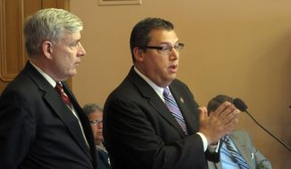 In this May 6, 2015 file photo, State Rep. Ron Hood, right, answers a question about his proposal to allow residents to carry a concealed weapon without first having to have a permit, with his co-sponsor, Rep. Tom Brinkman in Columbus, Ohio.  An Ohio House committee has scheduled a vote on legislation allowing individuals to carry concealed weapons without having to receive training, undergo a background check or obtain a license. The House Federalism Committee meets Wednesday, June 19, 2019  on the bill sponsored by Hood and  Brinkman, both Republicans.  (AP Photo/Andrew Welsh-Huggins, File) **FILE**