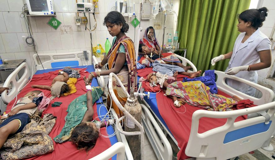 In this Tuesday, June 18, 2019 photograph, children showing symptoms of acute encephalitis syndrome undergo treatment at Sri Krishna Medical College Hospital in Muzaffarpur, Bihar state, India. More than 100 children have died in an encephalitis outbreak in India's eastern state of Bihar, authorities said Tuesday. (AP Photo/Aftab Alam Siddiqui)