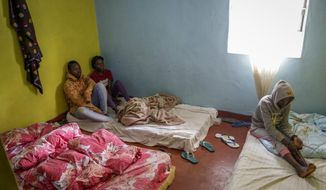 In this photo taken Tuesday, May 28, 2019, LGBT refugee Nina Muregwa, 17, left, from Burundi, who says she left Burundi after her lover's mother threatened to kill her, sits with others in the house where they take shelter in a low-income neighborhood of the capital Nairobi, Kenya. LGBT refugees allege they have been harassed by police in recent weeks in Kenya, which is a rare regional haven for the gay community yet maintains that gay sex is illegal. (AP Photo/Khalil Senosi)