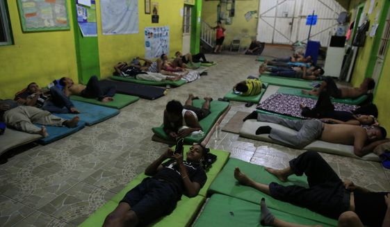 Male migrants bed down for the night on mattresses on the ground in the entry court of the Good Shepherd shelter in Tapachula, Mexico, Tuesday, June 18, 2019. Mexico's ramped-up effort to curb the flow of Central American migrants to the United States so far hasn't eased the burden on the dozens of independent humanitarian shelters like Good Shepherd that are scattered along migration routes through the country. (AP Photo/Rebecca Blackwell)