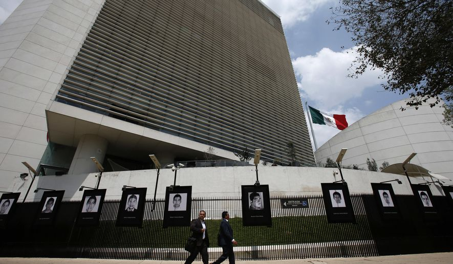 FILE - This Sept. 26, 2018 file photo shows the Senate building in Mexico City. Mexico's Senate has voted on Wednesday, June 19, 2019 to ratify a new free trade agreement with the United States and Canada, making it the first of the three countries to gain legislative approval. Hanging on the fence are the teachers college students who disappeared on Sept. 26, 2014. (AP Photo/Rebecca Blackwell, File)