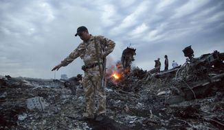 In this July 17, 2014, file photo, people walk amongst the debris at the crash site of a passenger plane near the village of Grabovo, Ukraine. An international team of investigators building a criminal case against those responsible in the downing of Malaysia Airlines Flight 17 is set to announce progress in the probe on Wednesday, June 19, 2019, nearly five years after the plane was blown out of the sky above conflict-torn eastern Ukraine. (AP Photo/Dmitry Lovetsky, File)